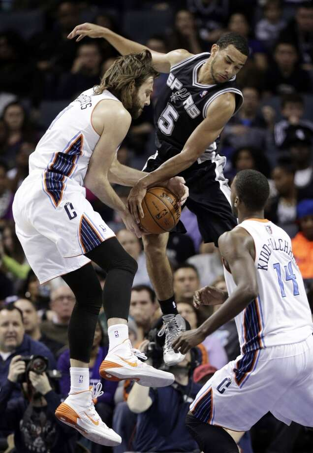 San Antonio Spurs' Cory Joseph, center, battles with Charlotte Bobcats' Josh McRoberts, left, for a rebound as Charlotte Bobcats' Michael Kidd-Gilchrist, bottom right, stands near during the second half of an NBA basketball game in Charlotte, N.C., Saturday, Feb. 8, 2014. The Spurs won 104-100. (AP Photo/Chuck Burton) Photo: Associated Press