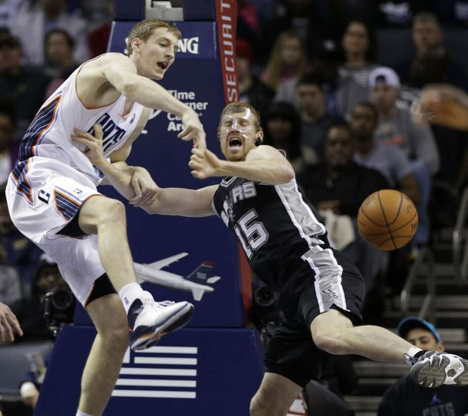 Charlotte Bobcats' Cody Zeller, left, and San Antonio Spurs' Matt Bonner, right, battle for a rebound during the first half of an NBA basketball game in Charlotte, N.C., Saturday, Feb. 8, 2014. (AP Photo/Chuck Burton) Photo: Associated Press