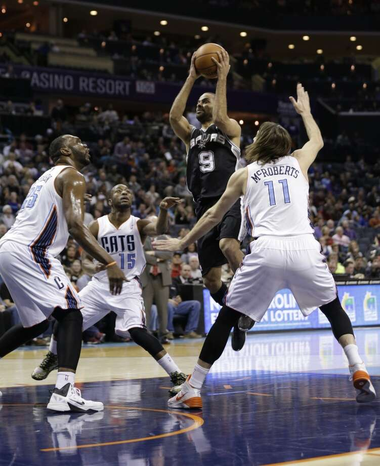 San Antonio Spurs' Tony Parker (9) drives to the basket against Charlotte Bobcats' Josh McRoberts (11) and Al Jefferson (25) during the first half of an NBA basketball game in Charlotte, N.C., Saturday, Feb. 8, 2014. (AP Photo/Chuck Burton) Photo: Associated Press