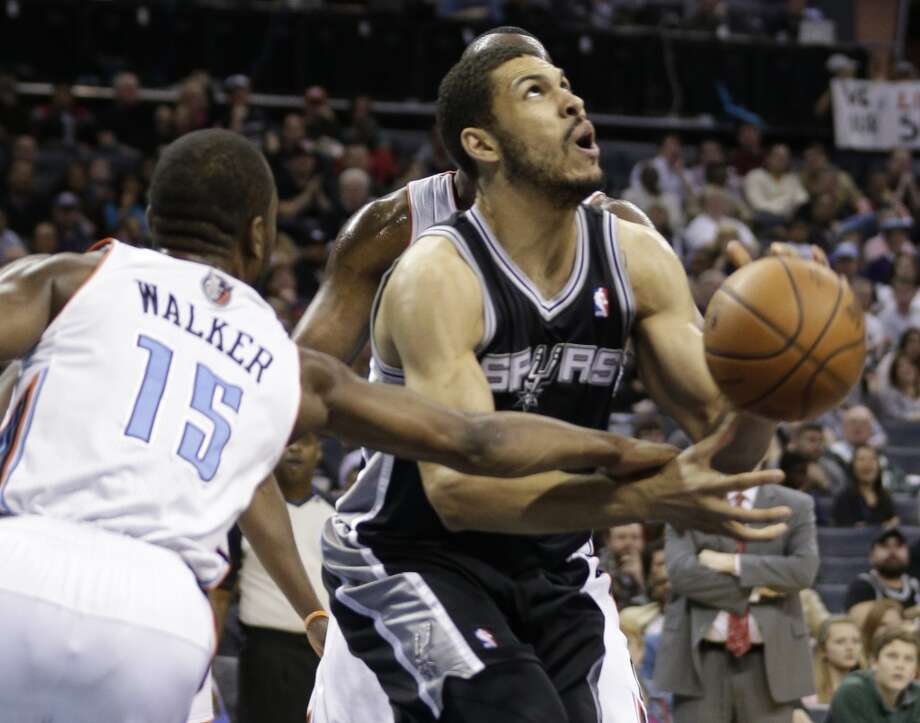 San Antonio Spurs' Jeff Ayres (11) is fouled as he drives between Charlotte Bobcats' Kemba Walker (15) during the first half of an NBA basketball game in Charlotte, N.C., Saturday, Feb. 8, 2014. (AP Photo/Chuck Burton) Photo: Associated Press