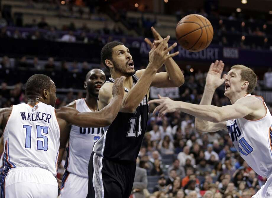 San Antonio Spurs' Jeff Ayres (11) is fouled as he drives between Charlotte Bobcats' Kemba Walker (15) and Cody Zeller (40) during the first half of an NBA basketball game in Charlotte, N.C., Saturday, Feb. 8, 2014. (AP Photo/Chuck Burton) Photo: Associated Press