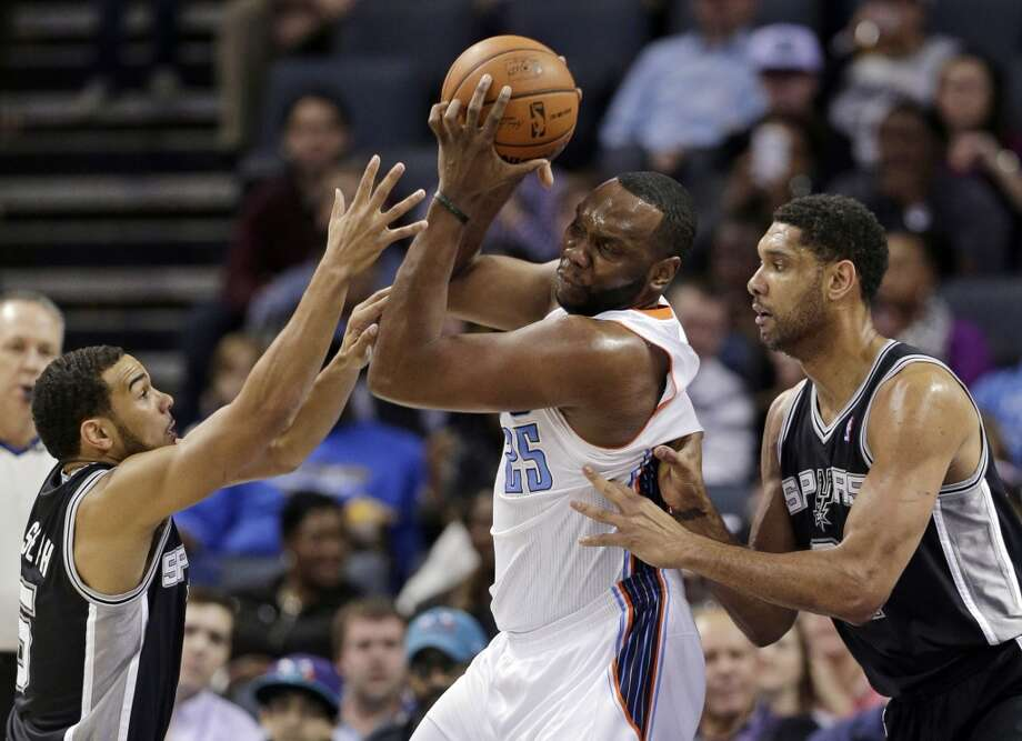 Charlotte Bobcats' Al Jefferson, center, is trapped by San Antonio Spurs' Tim Duncan, right, and Cory Joseph, left, during the first half of an NBA basketball game in Charlotte, N.C., Saturday, Feb. 8, 2014. (AP Photo/Chuck Burton) Photo: Associated Press