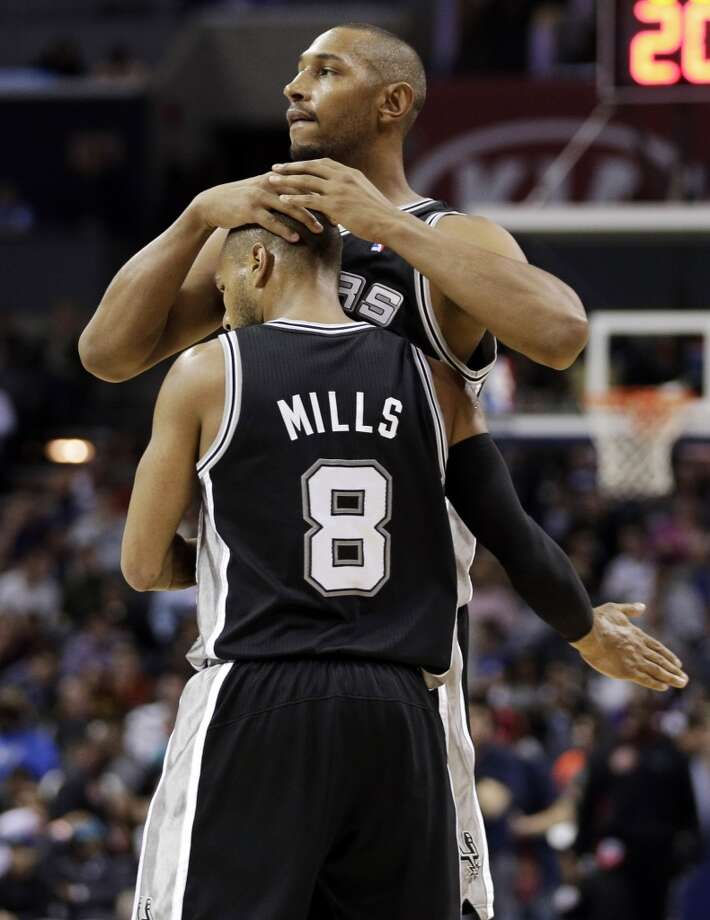 San Antonio Spurs' Boris Diaw, back, embraces teammate Patty Mills, front, after Mills' basket against the Charlotte Bobcats during the second half of an NBA basketball game in Charlotte, N.C., Saturday, Feb. 8, 2014. The Spurs won 104-100. (AP Photo/Chuck Burton) Photo: Associated Press