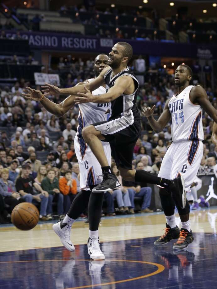 San Antonio Spurs' Tony Parker, center, is fouled as he drives past Charlotte Bobcats' Al Jefferson, left, and Michael Kidd-Gilchrist, right, during the first half of an NBA basketball game in Charlotte, N.C., Saturday, Feb. 8, 2014. (AP Photo/Chuck Burton) Photo: Associated Press