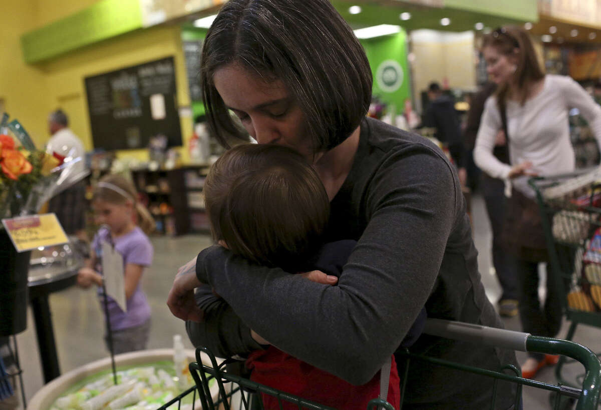 Nicole Dimetman kisses her son while waiting in the checkout line at Whole Foods in Austin on Saturday, Feb. 8, 2014.