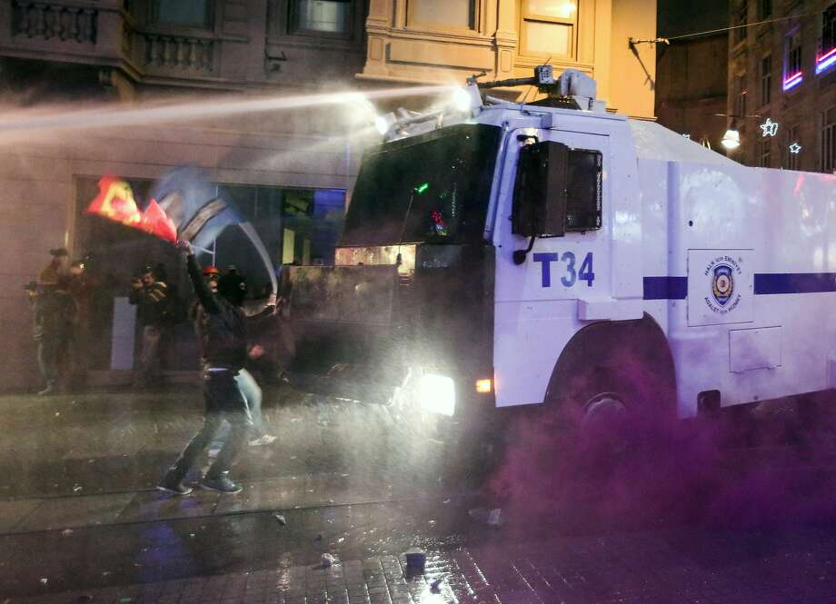 Turkish riot police fire water cannons and tear gas at hundreds of demonstrators who are trying to march to the city's main Taksim Square in Istanbul, Turkey, Saturday, Feb. 8, 2014, in protest of legislation which critics say will tighten government controls over the Internet. Demonstrators hurled firecrackers and stones Saturday at police officers who cordoned off Taksim Square. Many also denounced a corruption scandal involving former Cabinet ministers and called on the government to resign.(AP Photo/Emrah Gurel) Photo: Emrah Gurel, Associated Press