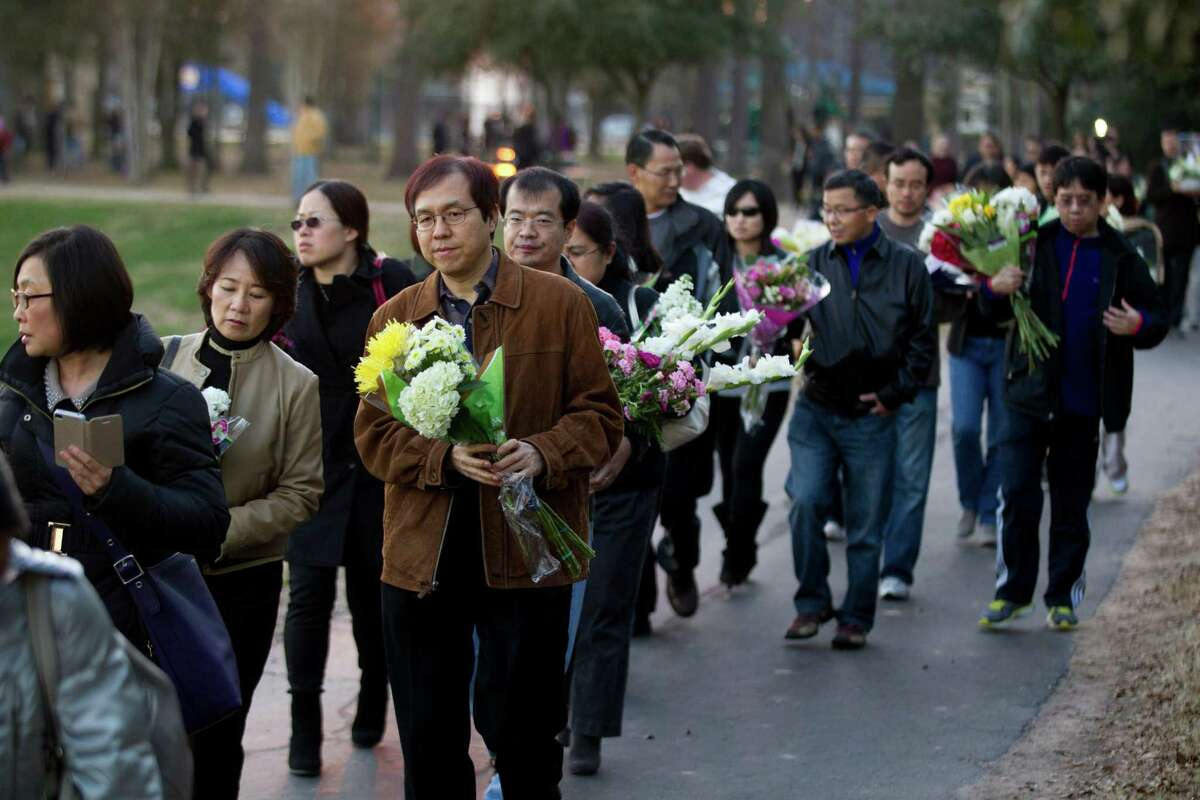 Mourners carry flowers to the home of the family shot to death in Cypress during a vigil organized by the Houston Chinese Alliance.