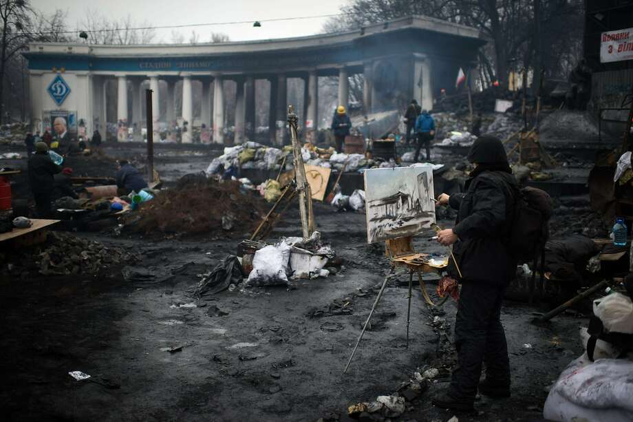 TOPSHOTS A man paints the scene as he stands near a barricade in Kiev, on February 8, 2014. Ukraine's embattled President Viktor Yanukovych returned to protest-hit Kiev on Saturday after holding talks with his Russian counterpart and ally Vladimir Putin about a suspended Moscow bailout loan. The chat late Friday on the sidelines of the opening ceremony of the Winter Olympic Games in Russia's Black Sea resort of Sochi came amid intensifying pressure from the opposition on Yanukovych to cede some of his broad powers and appoint a new pro-Western government.  AFP PHOTO / MARTIN BUREAUMARTIN BUREAU/AFP/Getty Images Photo: Martin Bureau, AFP/Getty Images