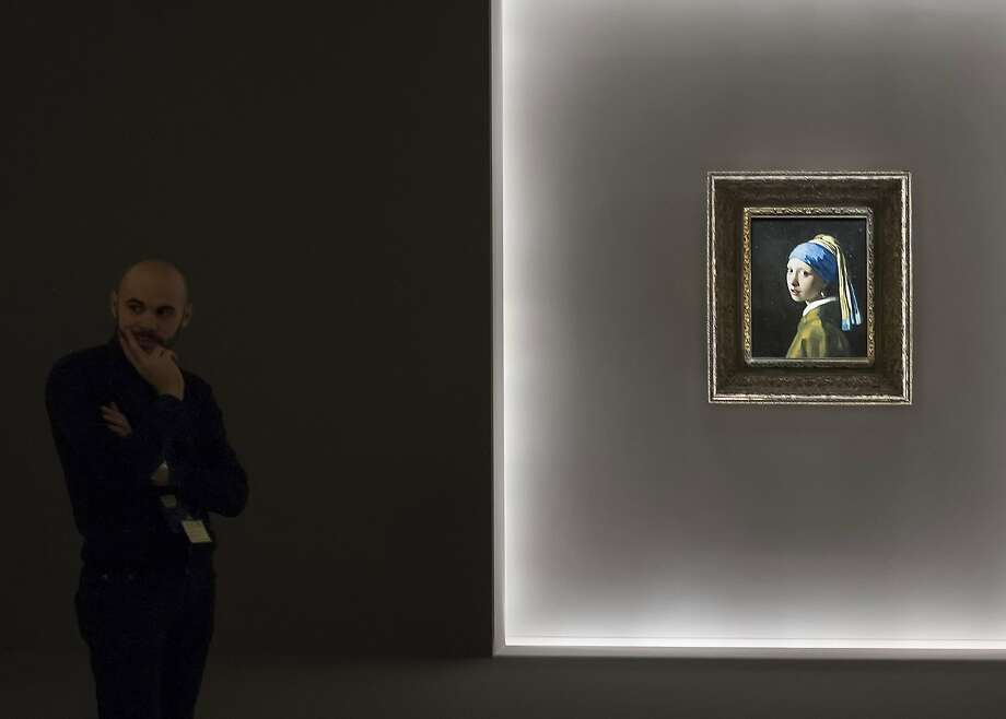 "BOLOGNA, ITALY - FEBRUARY 08:  A member of staff stands next to Vermeer's  ""La ragazza con l'orecchino di perla"" (The Girl with a Pearl Earring) at Palazzo Fava on February 8, 2014 in Bologna, Italy. The exhibition ""The Girl with a Pearl Earring"" will stay open until 25th May 2014.  (Photo by Marco Secchi/Getty Images) *** BESTPIX *** Photo: Marco Secchi, Getty Images"