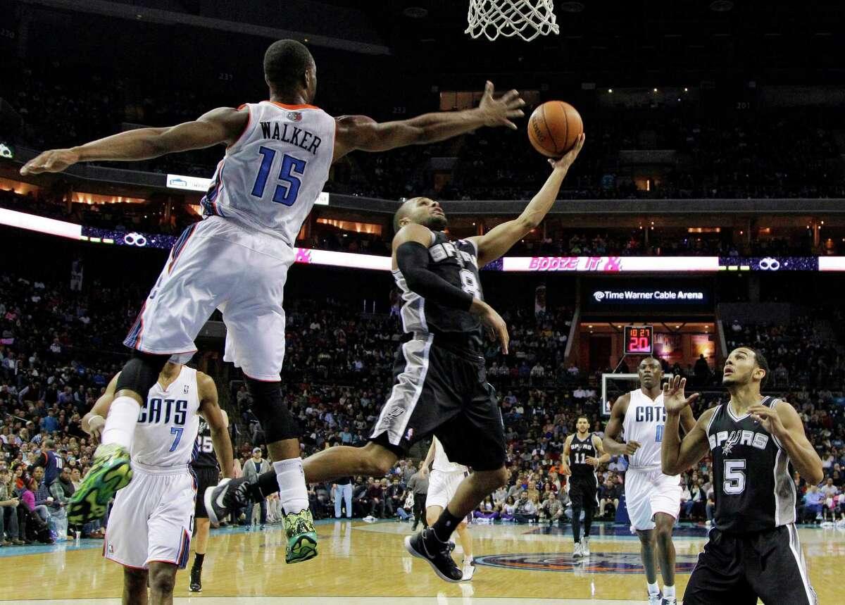 San Antonio Spurs' Patty Mills (8) drives past Charlotte Bobcats' Kemba Walker (15) during the second half of an NBA basketball game in Charlotte, N.C., Saturday, Feb. 8, 2014. The Spurs won 104-100. (AP Photo/Chuck Burton) ORG XMIT: NCCB110