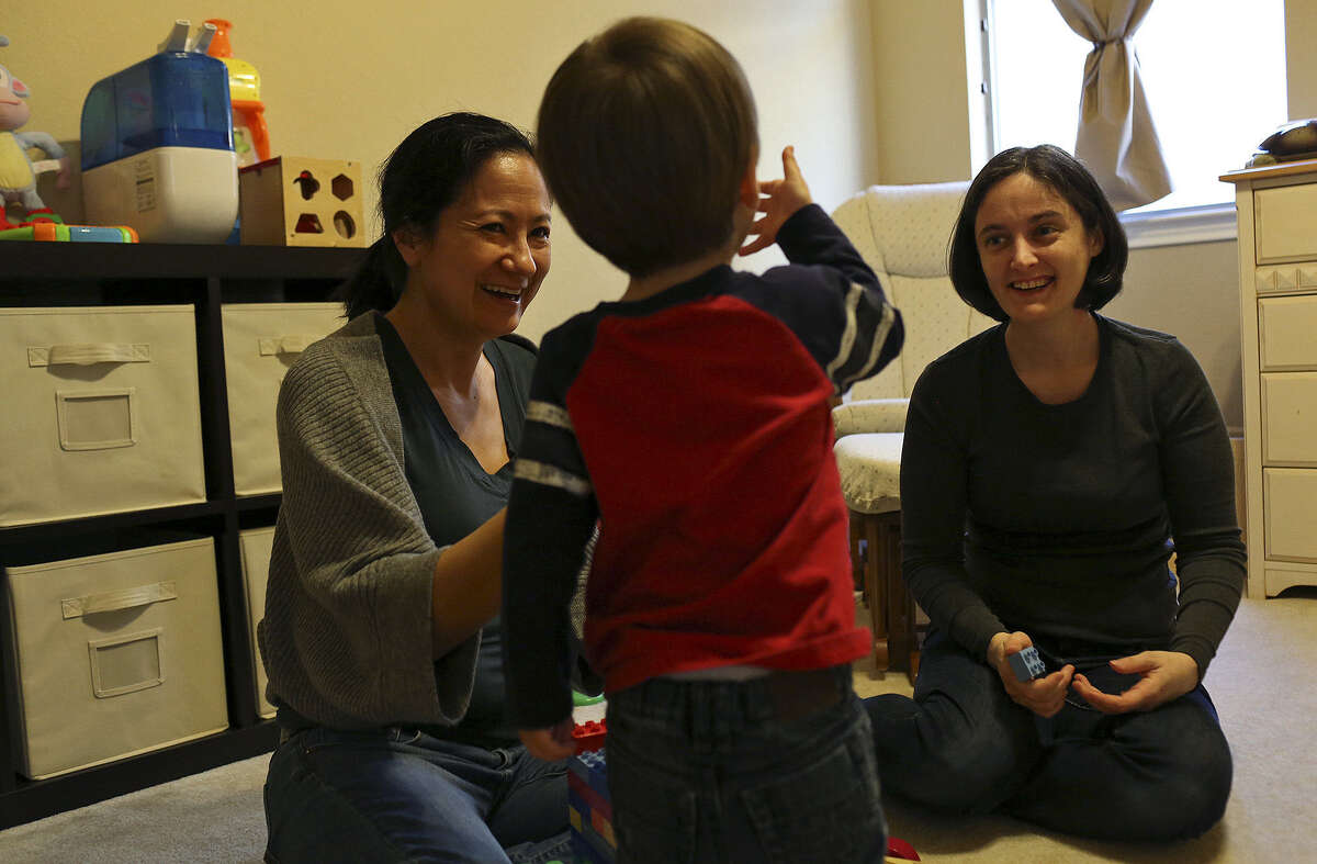 Cleo DeLeon (left) and Nicole Dimetman, playing with their son at home in Austin, met in San Antonio and are UTSA graduates.