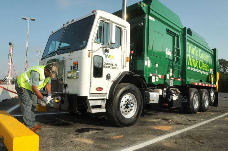 Servando Rosales, of Conroe, and a 14-year veteran of Waste Management, refuels his CNG-powered garbage truck at the slow-fill station. Photo: Jerry Baker, For The Chronicle