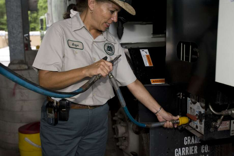 City of Lake Jackson Service Writer Gaye Shockley demonstrates the fuel filling connection on a city garbage truck which runs on compressed natural gas at the Lake Jackson, Texas city barn Wednesday, July 23, 2008. Photo: James Nielsen, Houston Chronicle