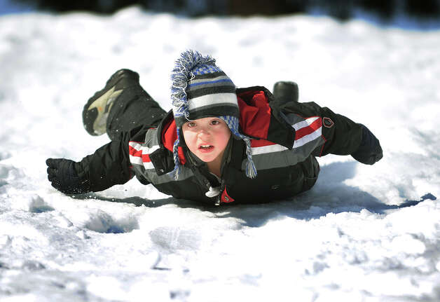 "Jayson Diaz, 7, of Stratford, tries ""penguining"", sliding down the hill on his belly without a sled, at Boothe Memorial Park in Stratford, Conn. on Sunday, February 9, 2014. The icy packed snow made the method quite effective. Photo: Brian A. Pounds / Connecticut Post"