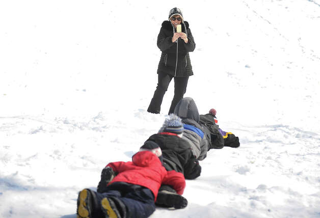 "Diane Sheridan, of Stratford, snaps a photo of her four grandsons as they ""penguin"" down the sled hill at Boothe Memorial Park in Stratford, Conn. on Sunday, February 9, 2014. Photo: Brian A. Pounds / Connecticut Post"
