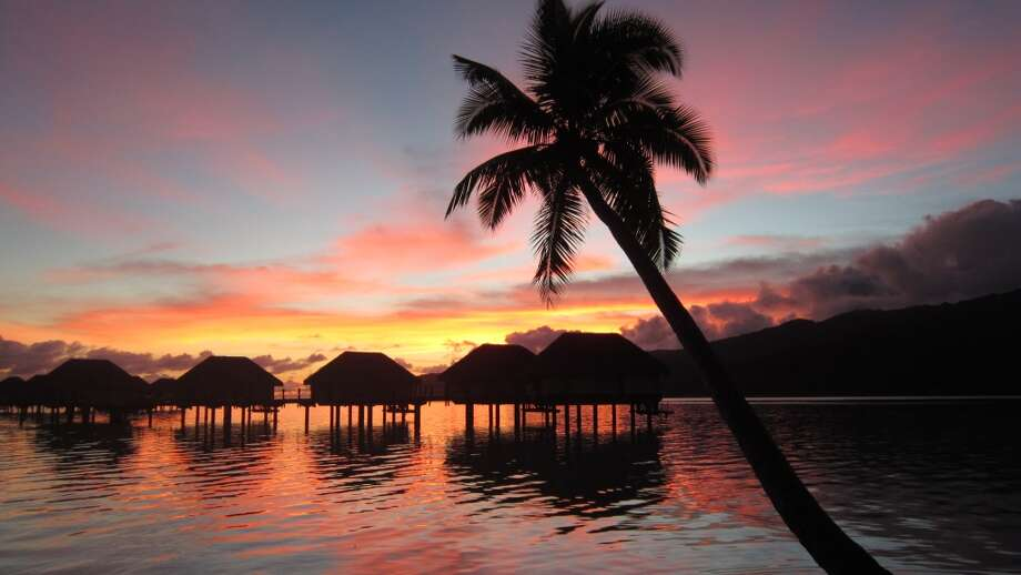French Polynesia's sensational sunsets come up to the doorsteps of over-the-water bungalows jutting out into a sparkling lagoon. Photo: Michelle Newman, For The Express-News