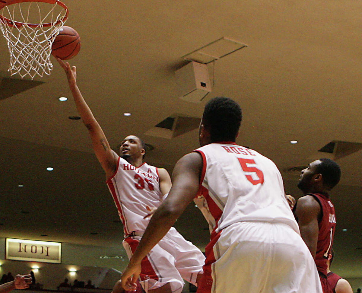 University of Houston forward TaShawn Thomas left, rolls the ball into the basket as teammate guard L.J. Rose center. looks on against Temple during the first half on men's college basketball game action at Hofheinz Pavilion Sunday, Feb. 9, 2014, in Houston.