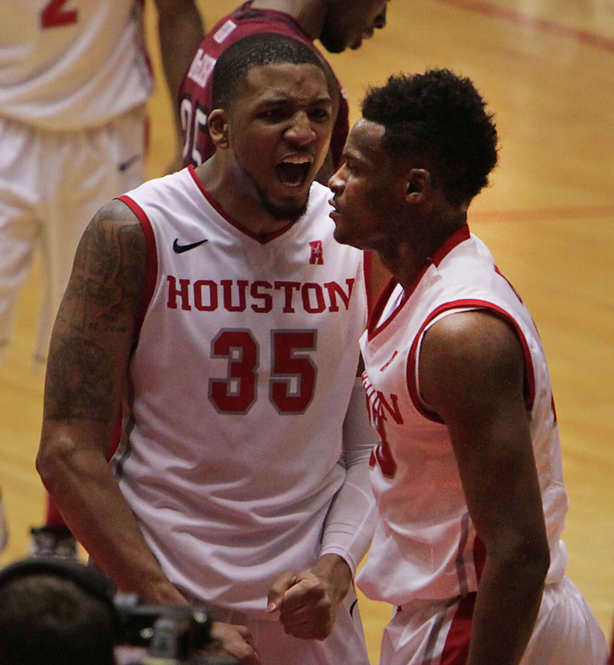 University of Houston's TaShawn Thomas left, reacts after teammate Danuel House right, slam dunked the ball against Temple during the second half of men's college basketball game action at Hofheinz Pavilion Sunday, Feb. 9, 2014, in Houston.