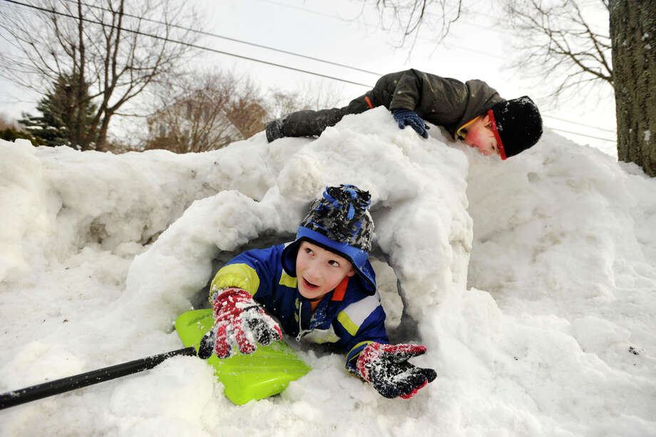 Joseph Sarno, bottom, and his brother, Ryan, play in the tunnel system they built in their front yard in Greenwich, Conn., on Sunday, Feb. 9, 2014. Photo: Jason Rearick / Stamford Advocate