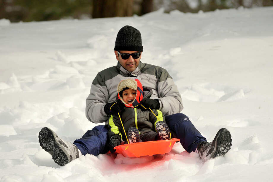 Shubhro Ghosh and his son, Tipu, sled down a hill in Bruce Park in Greenwich, Conn., on Sunday, Feb. 9, 2014. Sunday was both father and son's first time sledding. Photo: Jason Rearick / Stamford Advocate