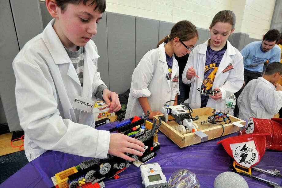 Members of the Perry Hill Dominators of Shelton from left Ian Pleasant, Megan Pereira and Amelia Nankervis work on their robots during the 6th annual Junior FIRST Lego League Exposition at the Academy of Information, Technology and Engineering in Stamford, Conn., on Sunday, Feb. 9, 2014. Photo: Jason Rearick / Stamford Advocate