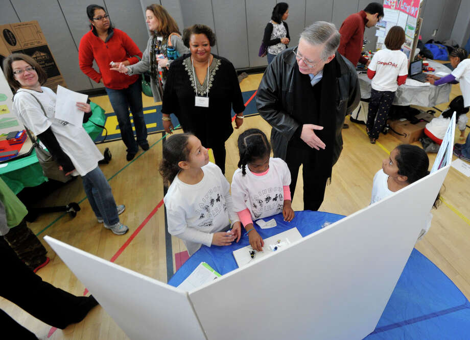 Mayor David Martin asks questions of the Danbury-based team Rainbow Girls from left, Sofia Velez, Mikaella Bernard and Trisha Chennuru during the 6th annual Junior FIRST Lego League Exposition at the Academy of Information, Technology and Engineering in Stamford, Conn., on Sunday, Feb. 9, 2014. The Junior FLL team's objective is to create a solution to a natural disaster using Legos and to explain it using poster board. Photo: Jason Rearick / Stamford Advocate