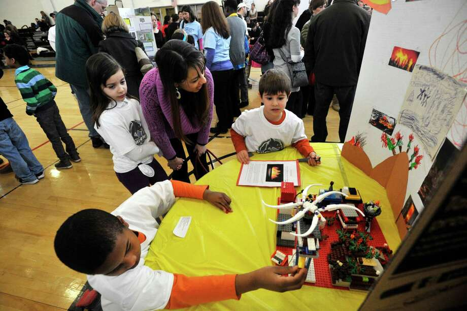 From K.T. Murphy school's Wildfire team Jake Biamonte, top right, explains his team's solution to a wild fire using legos and a display board to Tatiana Silva and her daughter, Gabriella, as Joel Perkins adds to the model during the 6th annual Junior FIRST Lego League Exposition at the Academy of Information, Technology and Engineering in Stamford, Conn., on Sunday, Feb. 9, 2014. The Junior FLL team's objective is to create a solution to a natural disaster using Legos and to explain it using poster board. Photo: Jason Rearick / Stamford Advocate