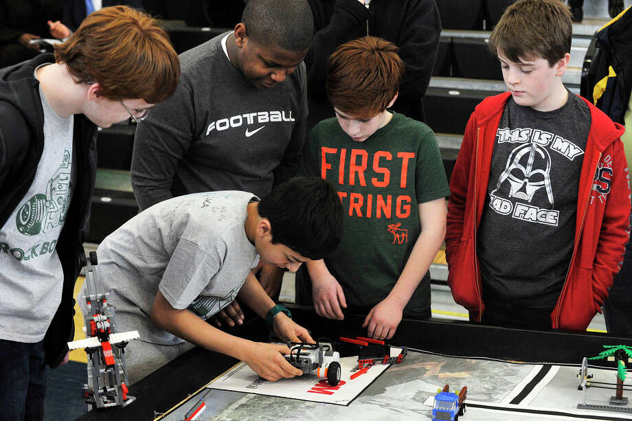 FIRST Lego League Rock Bots team members of Norwalk from left, Joel DeGrey, Javaughn DeCausy(top), Saloman Zapata, Luca Piacenza and Jack Caputo prepare to demonstrate their robot's abilities during the 6th annual Junior FIRST Lego League Exposition at the Academy of Information, Technology and Engineering in Stamford, Conn., on Sunday, Feb. 9, 2014. Photo: Jason Rearick / Stamford Advocate