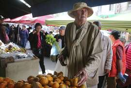 Frank Hatfield, 88, looks through the citrus at an open air produce stand in Chinatown on Tuesday Feb. 2, 2014 in San Francisco, Calif.