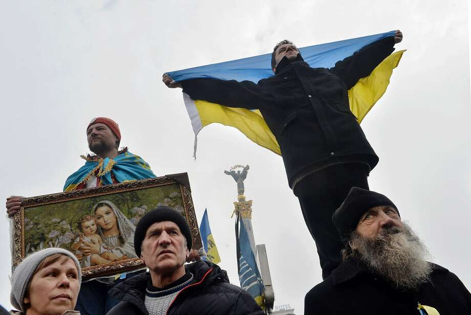 TOPSHOTS A man holds a religious icon while another holds up a Ukrainian flag during a mass opposition rally on Independence Square in Kiev on February 9, 2014. An estimated 70,000 pro-Western Ukrainians thronged the heart of Kiev on February 9 vowing never to give up their drive to oust President Viktor Yanukovych for his alliance with old master Russia. Wearing blue and yellow ribbons -- the colours of both Ukraine and the European Union -- the crowd received a religious blessing before opposition leaders took to a podium on Independence Square in a bid to ratchet up pressure on Yanukovych to appoint a new pro-Western government. AFP PHOTO/ SERGEI SUPINSKYSERGEI SUPINSKY/AFP/Getty Images Photo: Sergei Supinsky, AFP/Getty Images
