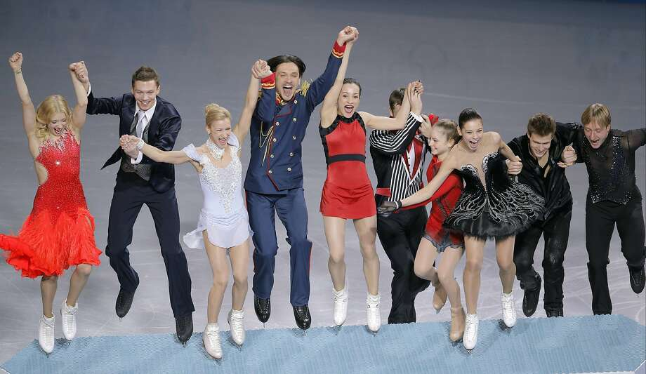 Russian figure skaters leap to the podium after winning gold in the team competition, a new Olympic event. Photo: Vadim Ghirda, Associated Press