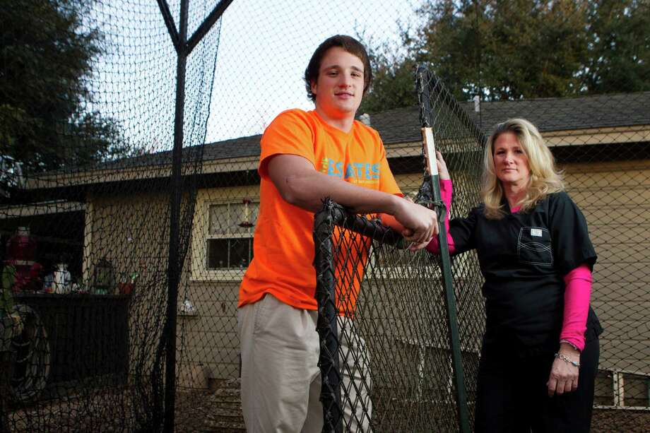 Grady Hefley, 17, poses for a portrait with his mother, Johanna, inside his batting cage in his back yard Wednesday, Feb. 5, 2014, in West University. Hefley suffered a number of concussions when he was 13. Photo: Brett Coomer, Houston Chronicle / © 2014 Houston Chronicle