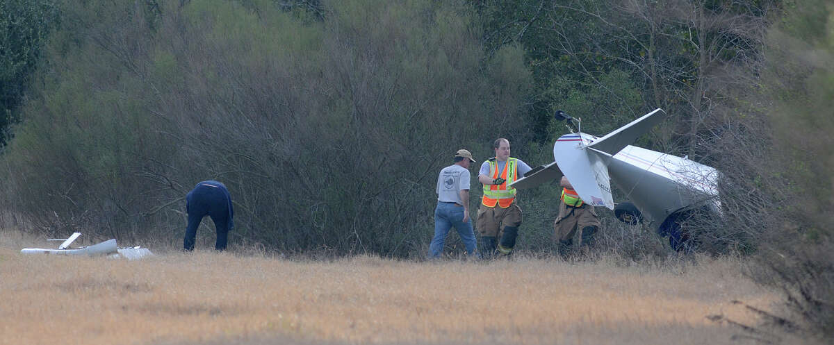 Members of the Klein Fire Dept. work the scene of a plane crash near Hooks Airport in Spring on Sunday afternoon.