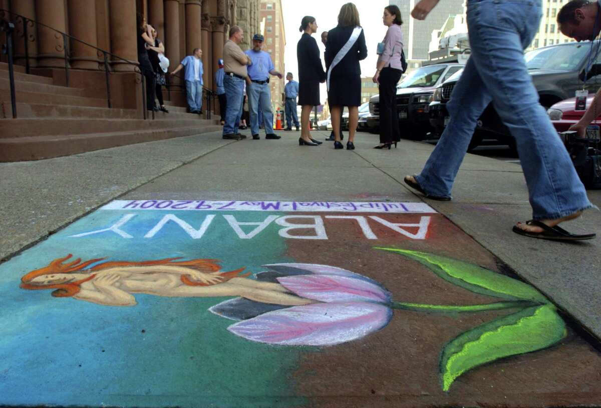 """Times Union Staff photograph by Philip Kamrass -- Artists Nina Stanley and Robyn Poirier of Albany took six hours to create a chalk drawing of """"Venus on the Half Tulip"""", their title, ( an ode to Botticelli's Renaissance painting""""The Birth of Venus"""", hanging in Florence, Italy) on the sidewalk in front of Albany's City Hall while a press conference to announce May's 56th annual Albany Tulip Festival, Monday April 19, 2004. Albany Tulip Queen 2003 Kaylin Gross wears a ribbon in the background, while Christina Collins, member of her court, is to her left."""
