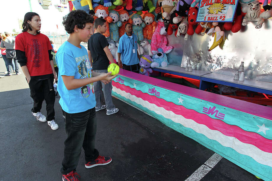 Robert Perez, 11, tries his luck at a game during the carnival at the San Antonio Stock Show and Rodeo, Sunday, Feb. 9, 2014. In back are friends, John Gonzales, 15, (red shirt) and Stefan Gonzales, 14, (black shirt). Photo: JERRY LARA, San Antonio Express-News / © 2014 San Antonio Express-News