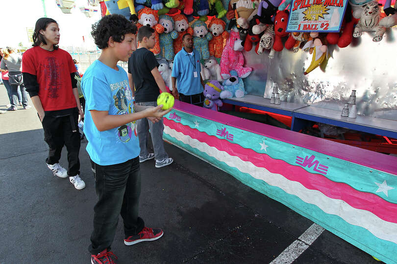 Robert Perez, 11, tries his luck at a game during the carnival at the San Antonio Stock Show and Rod