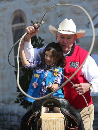 Sirena Aguero, 6, gets help with her roping from Dean Robeson, of the Cowboy Church, at the San Anto