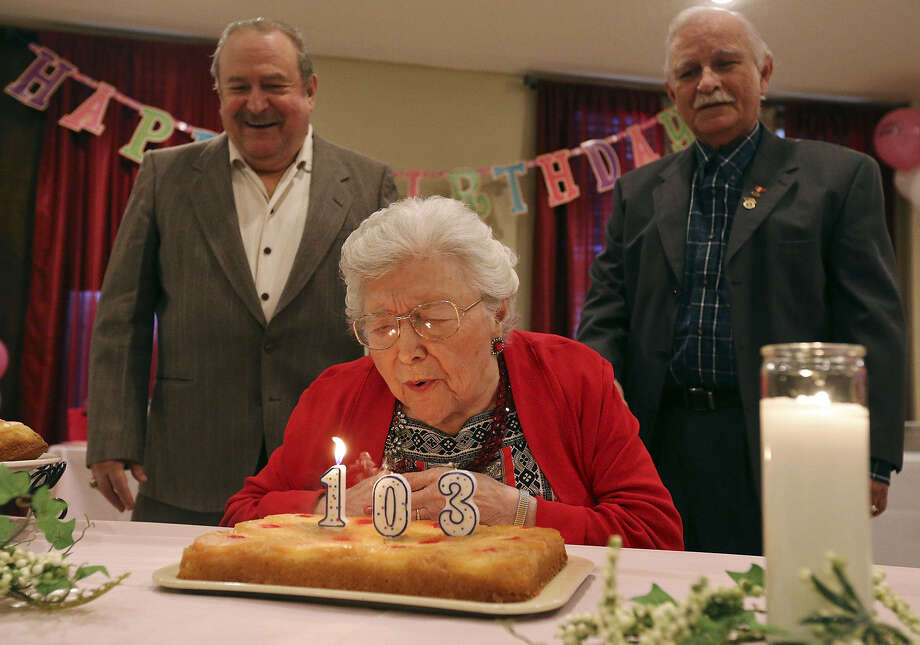 "Elvira Jimenez Chavez de Espinoza (center) blows out candles during her 103rd birthday party as her sons Edward Oliver Gonzalez (left) and Francisco ""Pancho"" Gonzalez watch. Photo: Edward A. Ornelas / San Antonio Express-News / © 2014 San Antonio Express-News"
