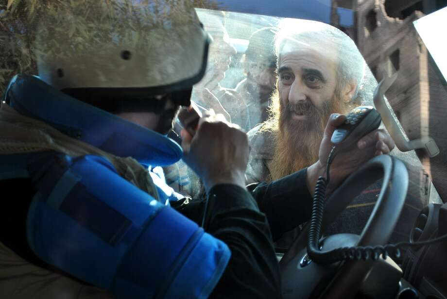A man looks at a United Nations (UN) staff member ahead of being evacuated from the besieged district of the central Syrian city of Homs to a safer location, on February 9, 2014. Aid teams evacuated hundreds of exhausted civilians from besieged districts of the city of Homs, as Syria's regime and rebels again accused each other of violating a truce.     TOPSHOTS/AFP PHOTO/BASSEL TAWILBASSEL TAWIL/AFP/Getty Images Photo: Bassel Tawil, AFP/Getty Images