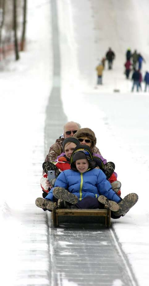 A group rides on the Eagles Mere Toboggan Slide in Eagles Mere, Pa., Sunday, Feb. 9, 29014. The slide is part of a fundraiser for the local volunteer fire company. (AP Photo/Sun-Gazette, Mark Nance) Photo: Mark Nance, Associated Press