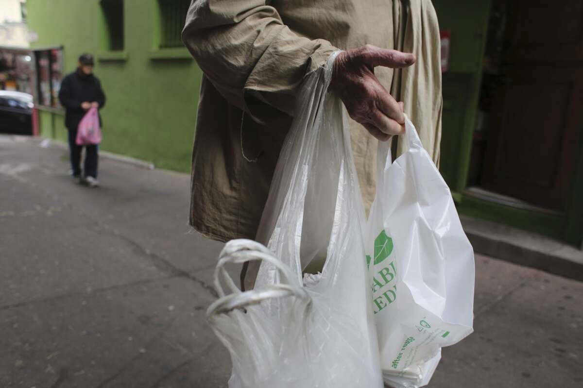 Carrying his signature collection of plastic bags, Frank Hatfield, 88, makes his rounds through Chinatown on Tuesday Feb. 2, 2014 in San Francisco, Calif.