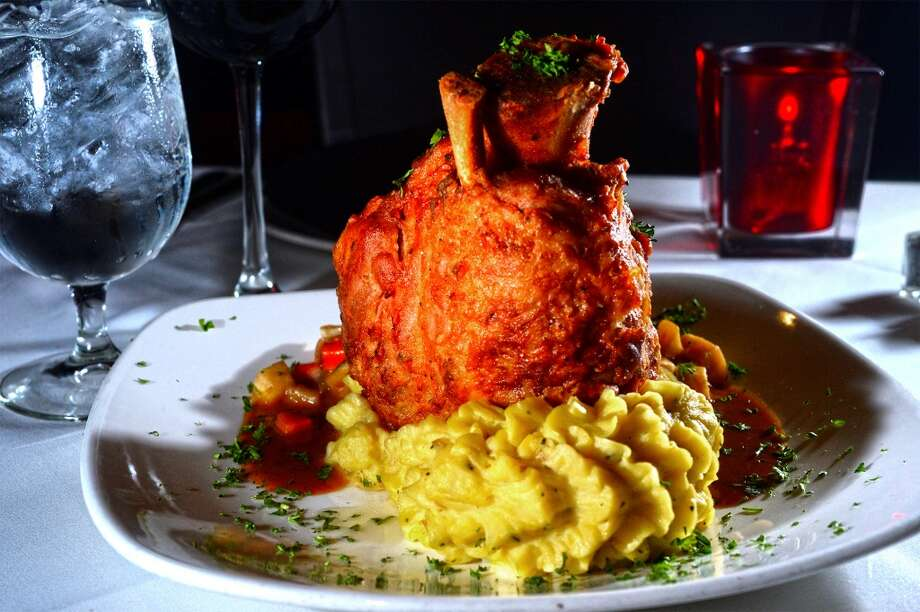 The Grill's crispy pork shank is served bone in with a demi glaze, mashed potatoes and root vegetables.  Photo taken Wednesday, January 22, 2014 Guiseppe Barranco/@spotnewsshooter