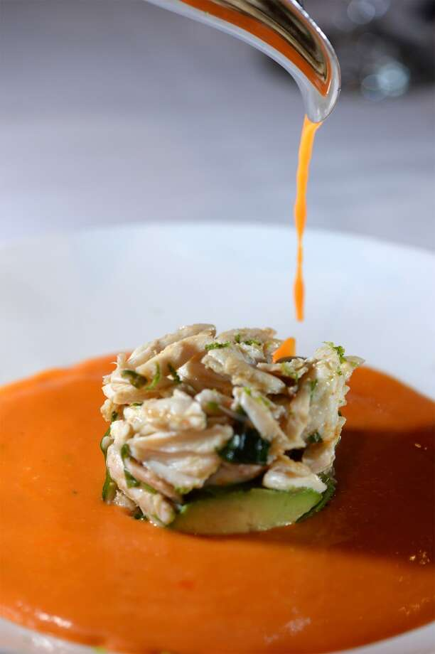 Red pepper bisque poured over a citrus crab salad at The Grill.  Photo taken Wednesday, January 22, 2014 Guiseppe Barranco/@spotnewsshooter