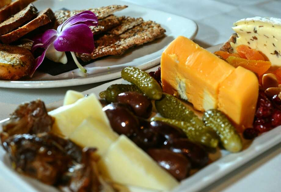 The Grill's three cheese plate rotates a variety of cheeses served with dried fruit, olives and nuts. Photo taken Wednesday, January 22, 2014 Guiseppe Barranco/@spotnewsshooter