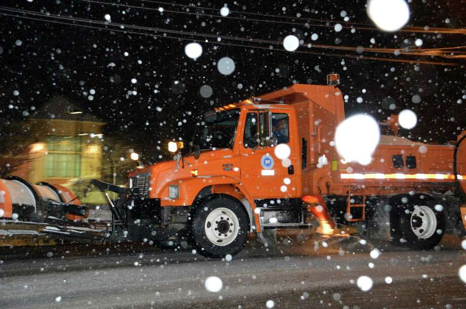 Plow trucks hit the Post Road late Sunday as the latest winter storm unleashed light snowfall across the region. Photo: Jarret Liotta / Westport News contributed