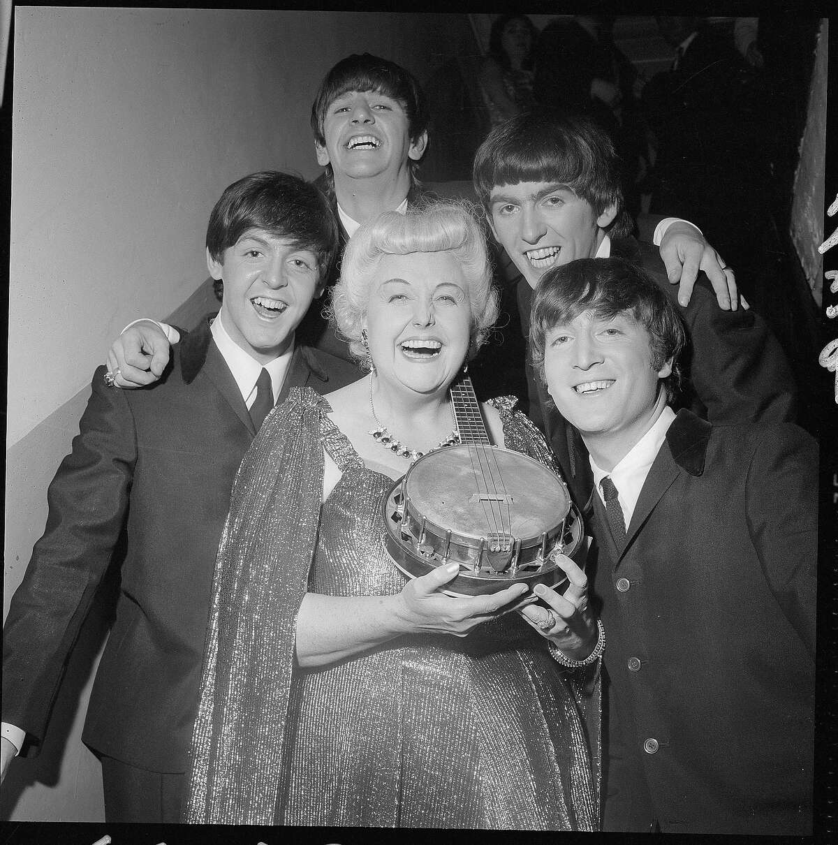 """The Beatles take a break backstage with singer and banjo player Tessie O'Shea who is probably best known for the song """"Two Ton Tessie from Tennessee,"""" despite being Welsh."""