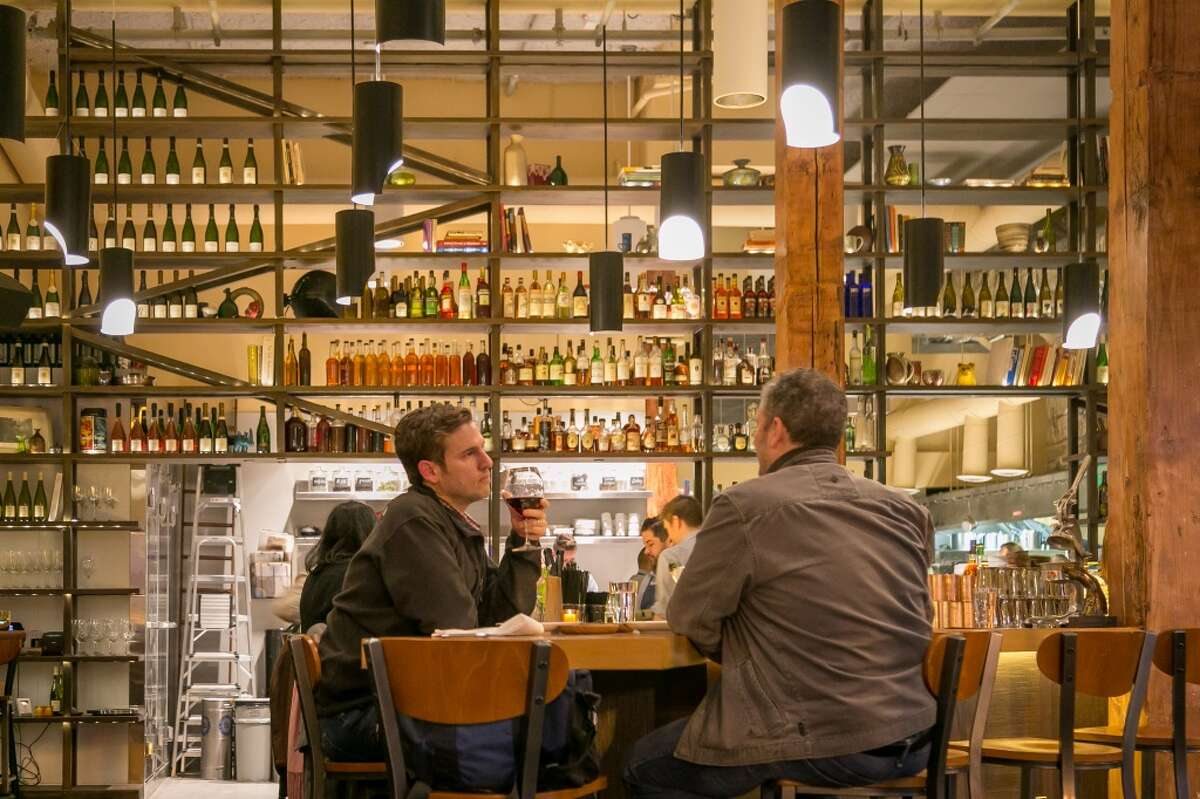 People enjoy dinner at the bar at Alta CA in San Francisco.