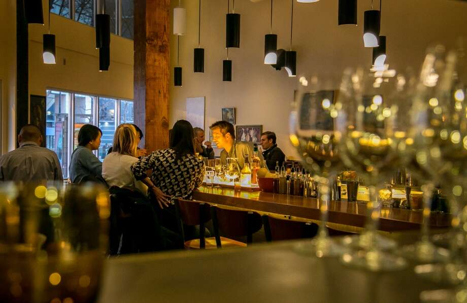 People enjoy dinner at the bar at Alta CA in San Francisco. Photo: John Storey, Special To The Chronicle