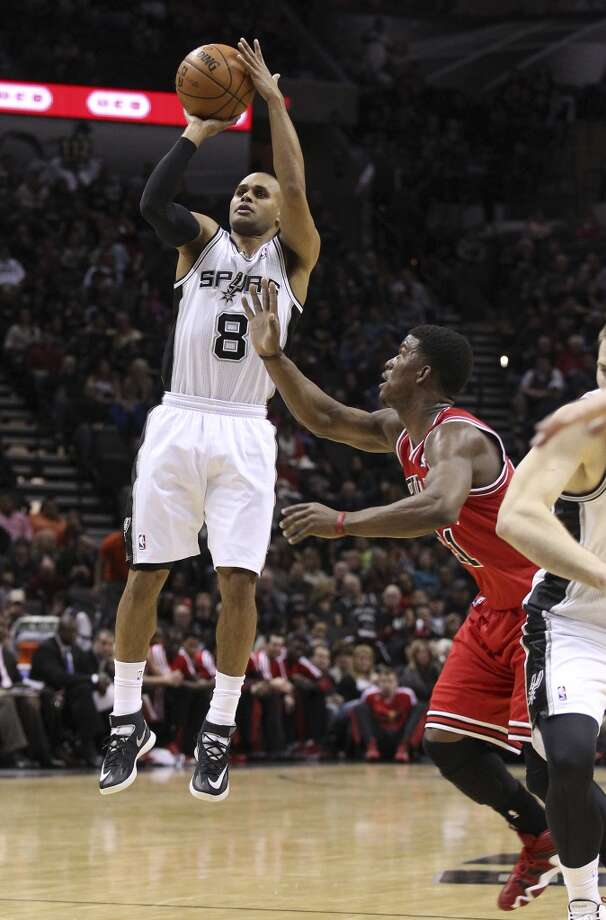 Spurs' Patty Mills (08) takes a three-pointer against Chicago Bulls' Jimmy Butler (21) at the AT&T Center on Wednesday, Jan. 29, 2014. Photo: Kin Man Hui, San Antonio Express-News