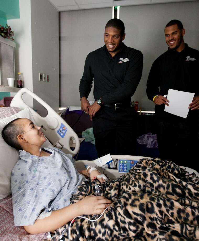 Michael Sam, center, and UCLA linebacker Anthony Barr, right, visit with 16-year-old cancer patient, Maddy Batiz, 16, at Texas Children's Hospital on Dec. 11, 2013. Sam and Barr, along with University of Alabama linebacker C.J. Mosley, and University of Pittsburgh defensive tackle Aaron Donald were finalists for the Rotary Lombardi Award. Photo: Cody Duty, Houston Chronicle